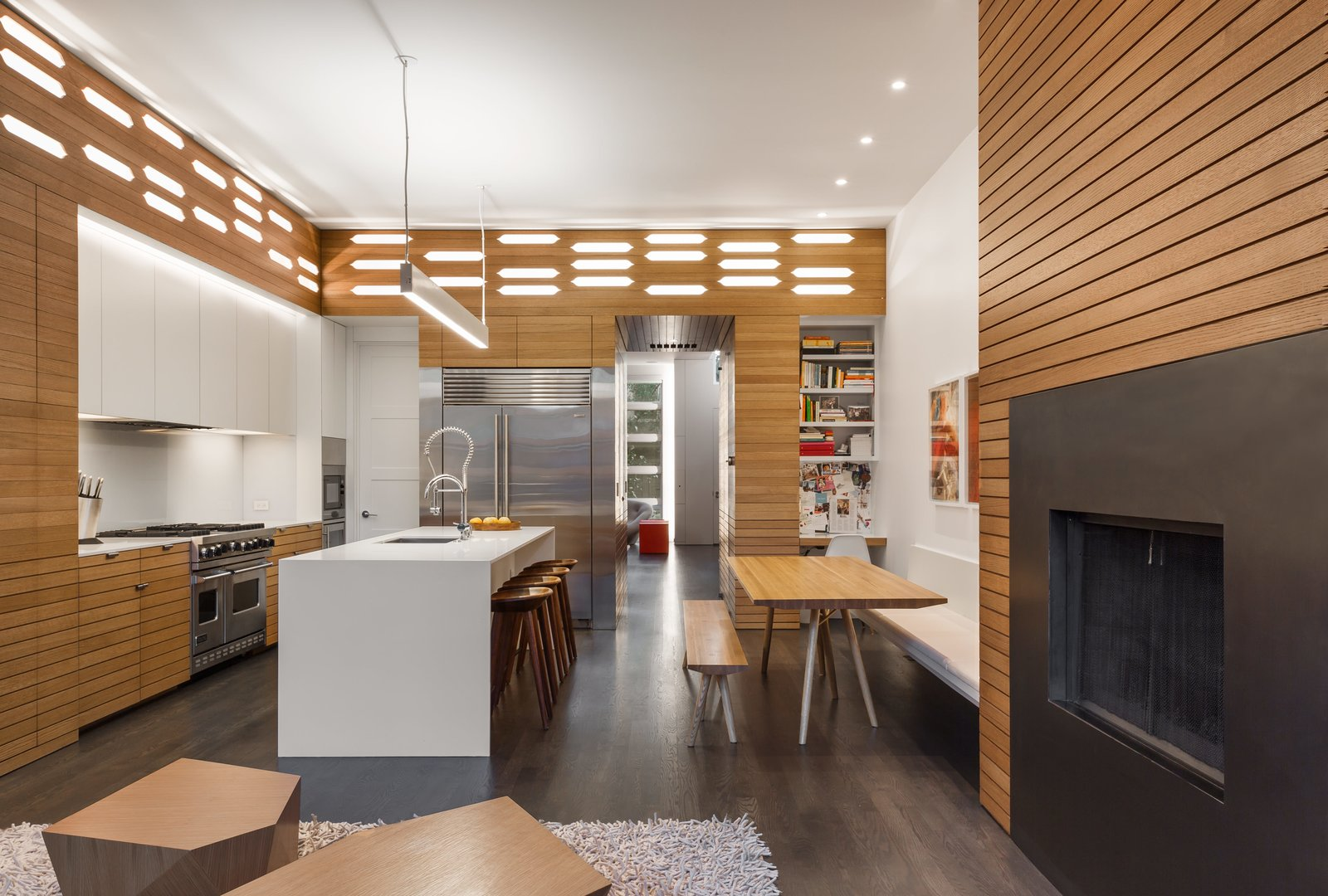White Cabinet, Refrigerator, Dark Hardwood Floor, Track Lighting, Dining Room, Bench, Standard Layout Fireplace, and Table Lutron smart controls manage the new kitchen's abundance of lighting options, including an Axis twin-beam pendant that hangs directly over the island.  Photo 2 of 16 in Four Floors of Gadgets and Gardens in Chicago