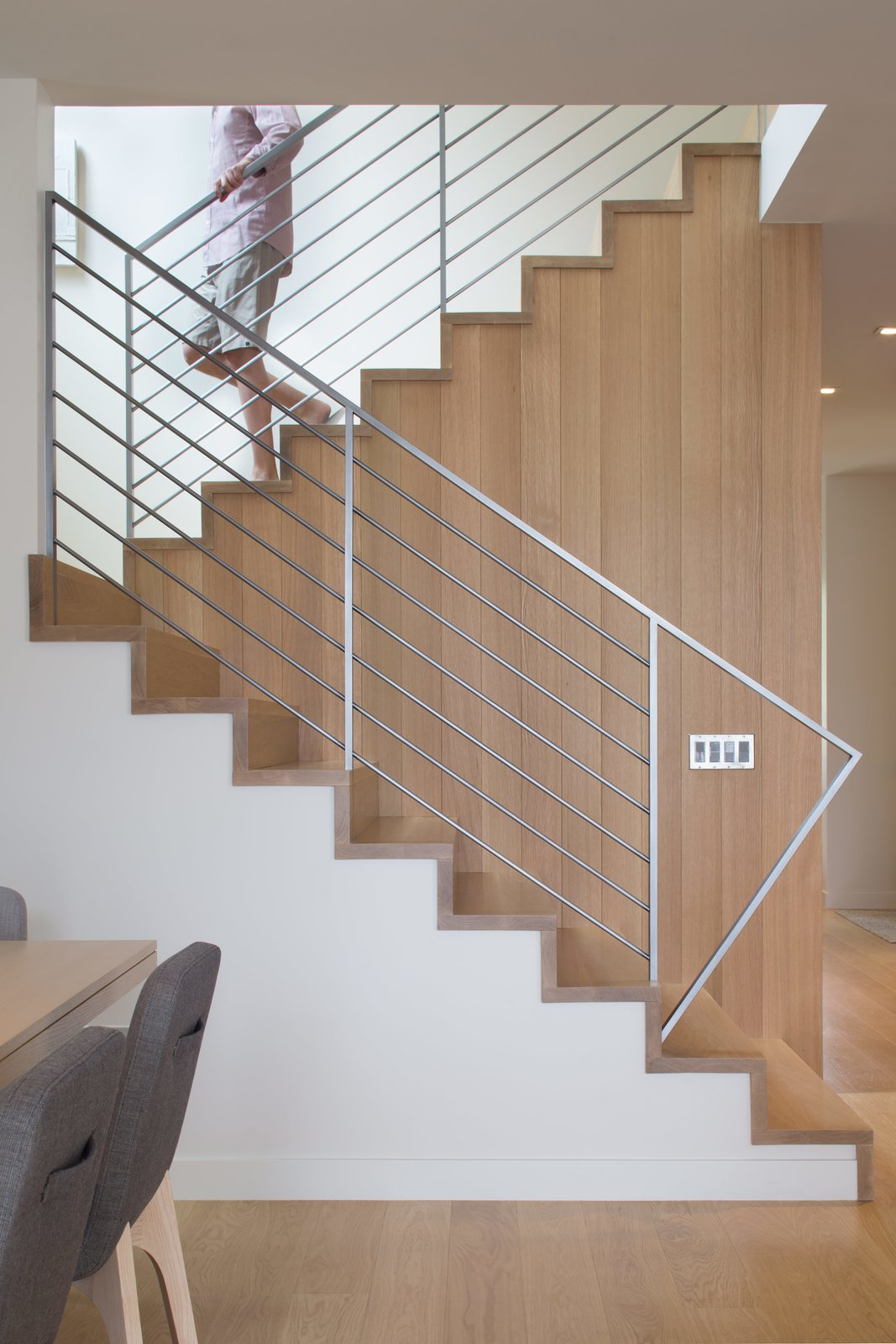 """Staircase, Metal Tread, Metal Railing, and Wood Tread The materials are limited to white millwork and white oak. """"When we come home, we want something serene,"""" Broughton says.  Photo 7 of 8 in How One Aspen House Lives Up to LEED"""