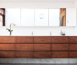 Architect Paul Syme designed custom storage units with dark-stained walnut fronts that provide a place for everything in his clients' Toronto bathroom. The wall-to-wall mirror and the Corian counter are custom, and the faucets are by Vola.