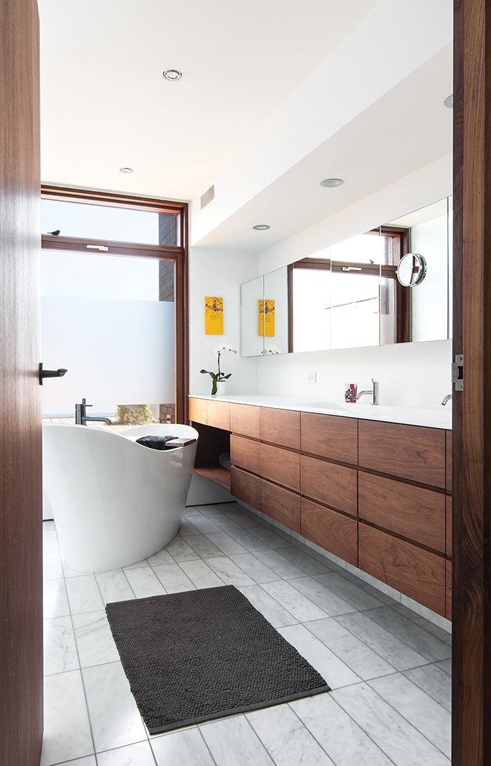 Bath Room, Freestanding Tub, and Marble Floor The bathtub faces a Spanish-cedar-framed window overlooking the back deck. Once the outside plants have grown up enough to provide privacy, the adhesive film on the window will be removed.  Photo 3 of 13 in A 1930s Tudor Home Brightens Up in Toronto