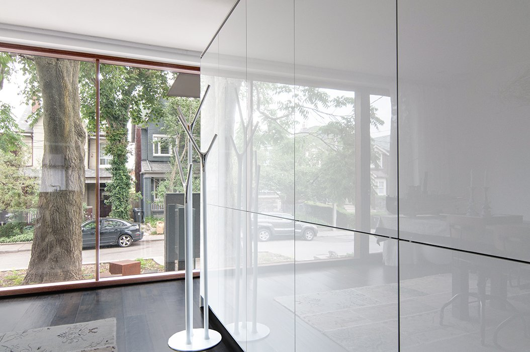 On the ground floor, freestanding cabinetry with a gloss lacquer finish by Bulthaup separates the entryway from the kitchen and dining area.  Photo 10 of 13 in A 1930s Tudor Home Brightens Up in Toronto