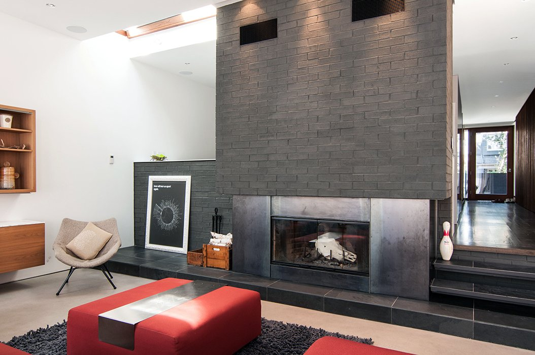 A slight gap between the existing house and the new addition allows for a skylight and a masonry chimney with a wood-burning fireplace.  Photo 11 of 13 in A 1930s Tudor Home Brightens Up in Toronto