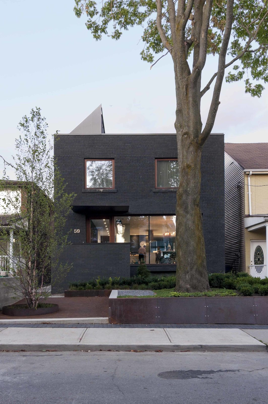 The transformed facade features dark gray stained-masonry.  Photo 12 of 13 in A 1930s Tudor Home Brightens Up in Toronto