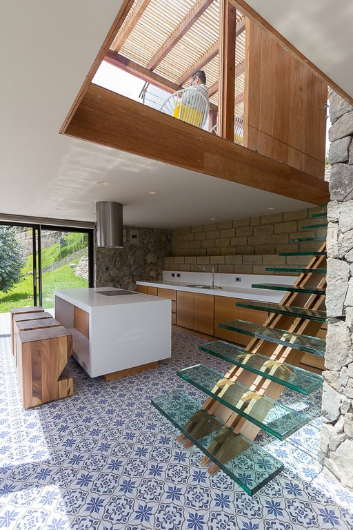 Staircase In the kitchen, a staircase with a wood backbone supports floating glass treads. The home's main entrance is located on the top level, due to the property's incline.  K I T C H E N S from Tourists to Ecuador Hope to Get Near This Home's Lookout