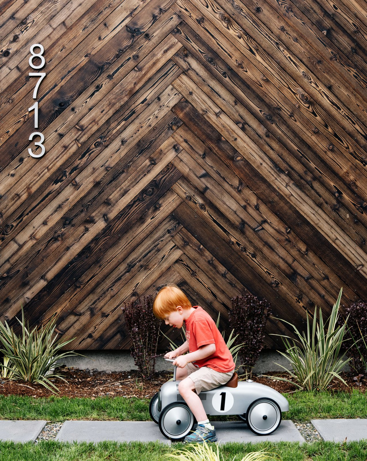 Passive House wood exterior with child riding toy car across grass lawn.
