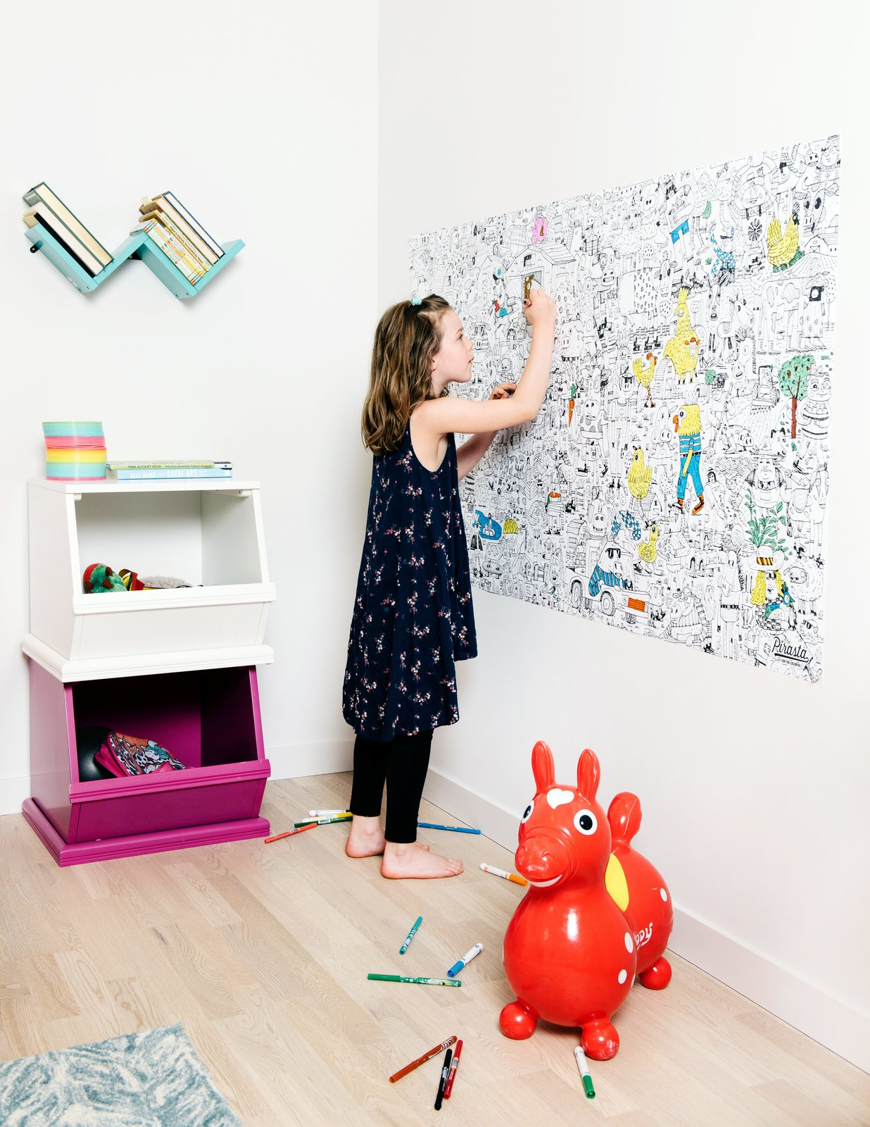 Passive House children's room with child coloring on large coloring book wall poster.