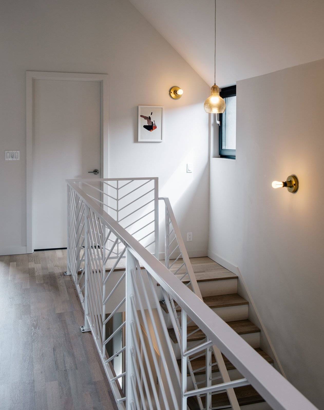 Passive House staircase with white steel railing and wood tread.