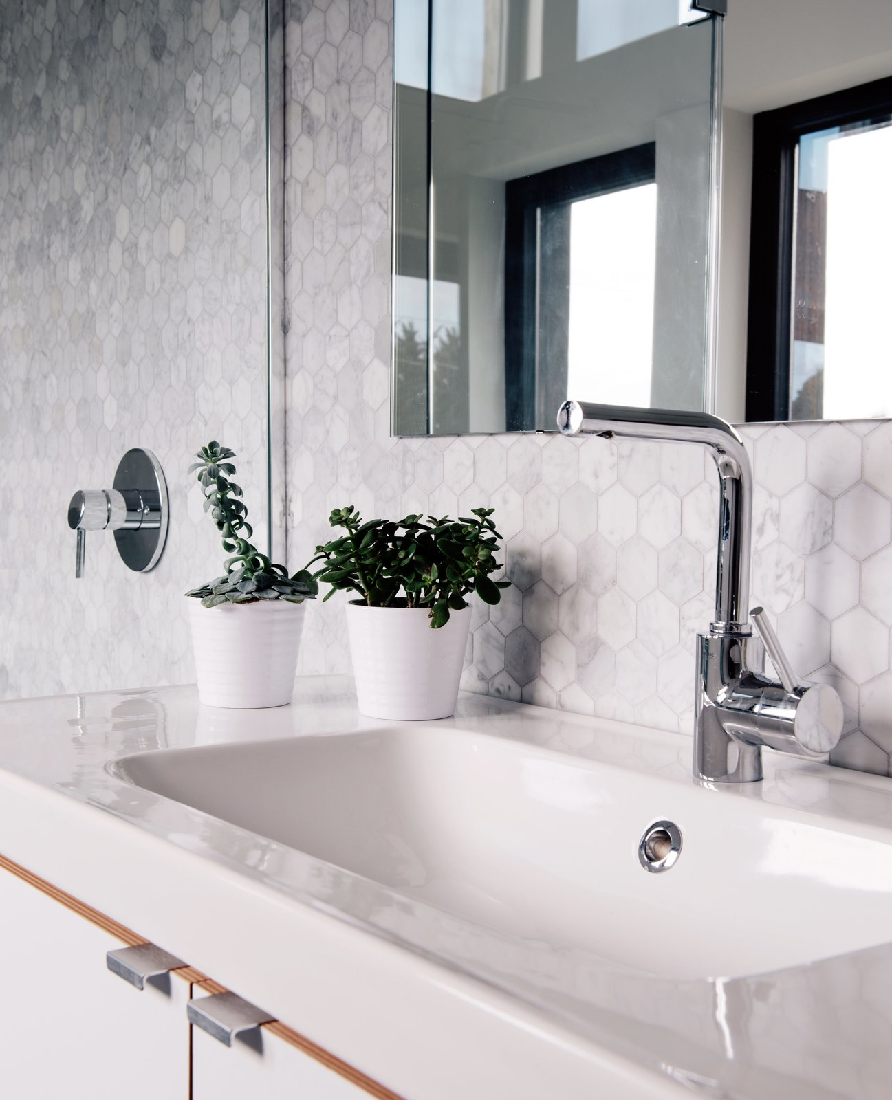 Passive House bathroom white drop-in sink and stainless steel silver faucet.