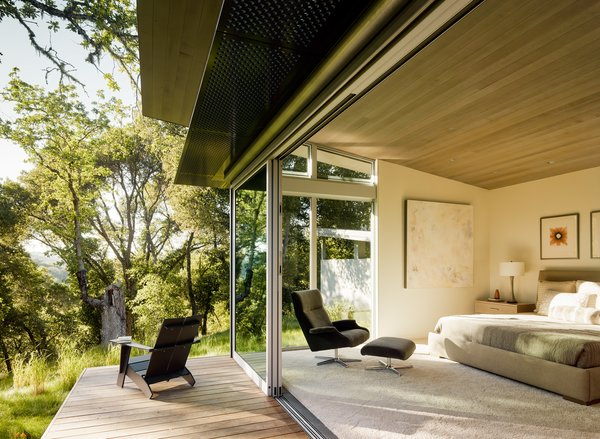 "Sloped ceilings, covered with stained Western red cedar, add warmth to the interior (bottom). ""We set out to design using the best of what modernism has to offer, but to try to execute that in a way that is livable and home-like,"" says architect Jonathan Feldman. The bedroom contains an A. Rudin bed and a Beau chair from Room & Board. It opens onto a deck with an aluminum awning"