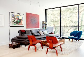 The main floor is arranged as one long, contiguous space, with a living area and balcony at the front end. An Aulia coffee table by Henk Vos, a pair of red Eames molded plywood chairs, and a Pelican chair by Finn Juhl center the space.