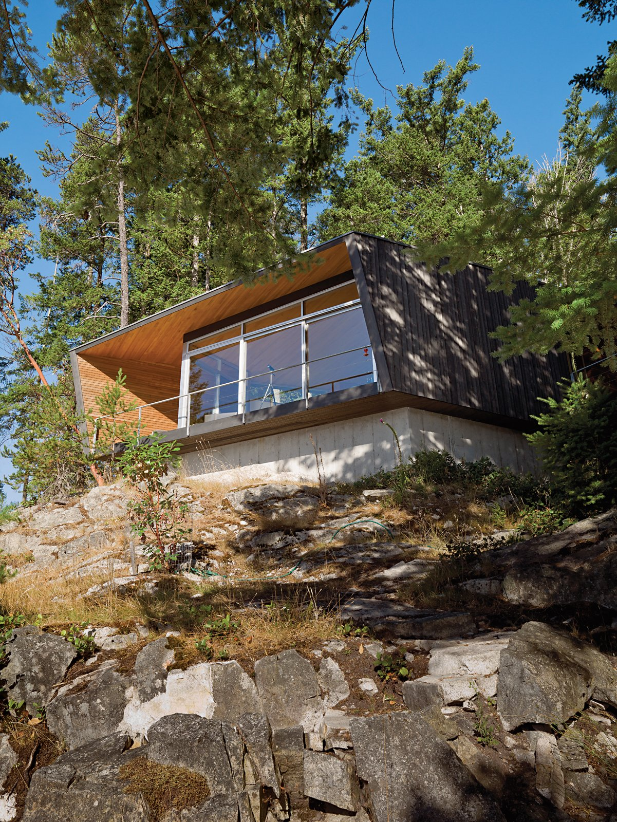 Outdoor, Slope, Trees, Boulders, and Shrubs Perched over a cliff face, the hooded deck of the Gambier Residence reads like a ship's prow over Howe Sound, the scenic waters near Vancouver.  Photo 2 of 9 in When Living on the Edge is Super Comfortable