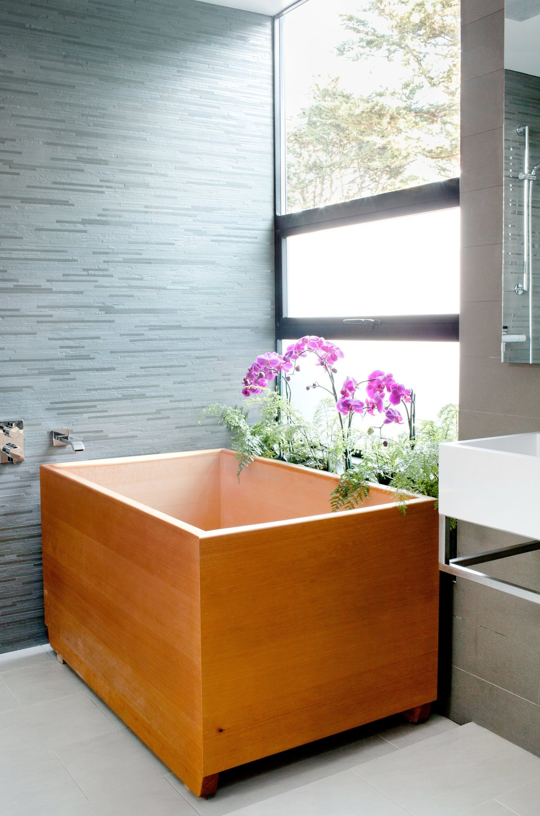 Charred House bathroom with wood atandalone tub and flowers