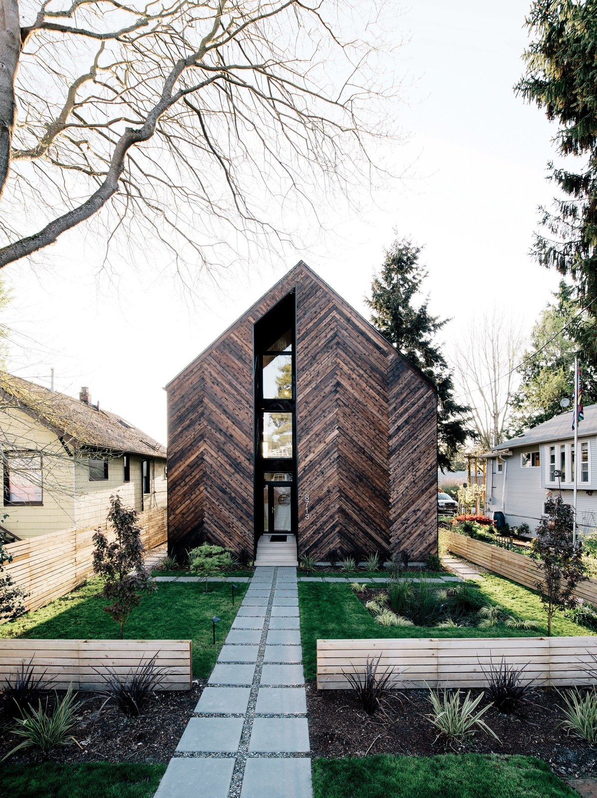 Passive House wood exterior with grass lawn.