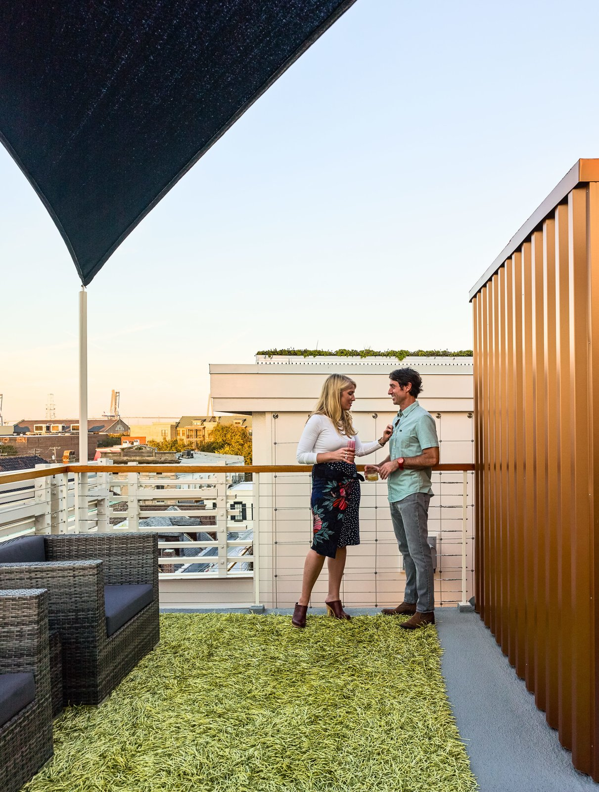 Outdoor, Rooftop, Metal Fences, Wall, and Wire Fences, Wall The cable railing around the perimeter of the deck is capped with a banister made of reclaimed river cypress.  Photo 6 of 7 in High Above Traditional Charleston, a Modern Home Finds its Roost