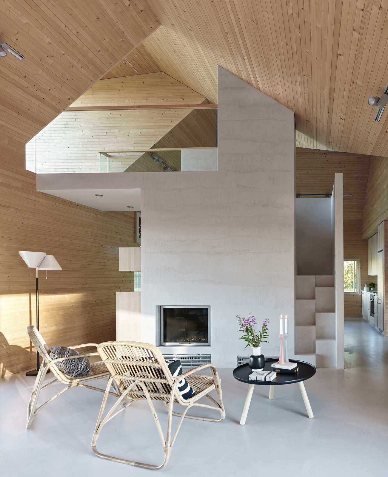 Living Room, Chair, Coffee Tables, Ceiling Lighting, Floor Lighting, Concrete Floor, and Wood Burning Fireplace The living room includes a table from Normann Copenhagen, chairs by Annansilmät-Aitta, and Alvar Aalto's A810 lamp for Artek, all on a poured concrete floor.  Photo 5 of 8 in This Battery-Powered House Never Runs Out of Juice