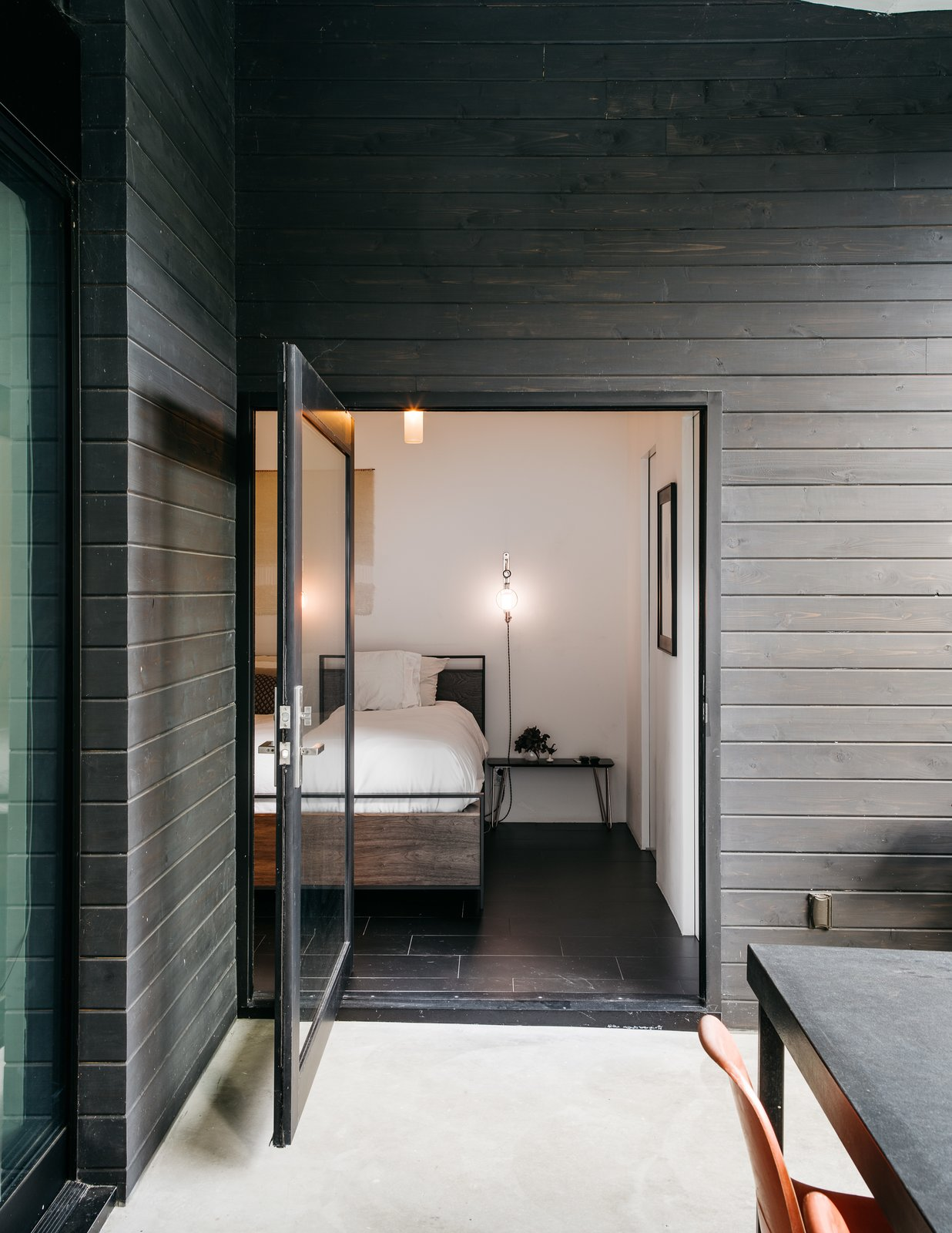 Bedroom, Bed, Ceramic Tile Floor, Night Stands, and Wall Lighting The patio is accessed from the master bedroom via a large pivot door. The bed and mirror are from Crate and Barrel; the pendant is from Droog. The couple made the wall sconces themselves.  Photo 5 of 10 in This Los Angeles Home is Driven by Automotive Design