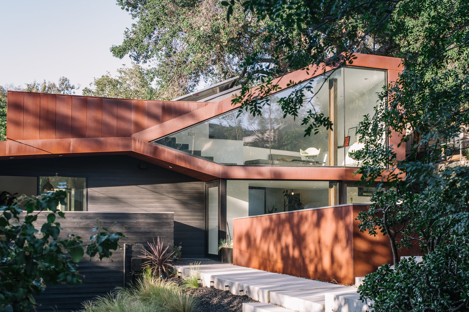 Exterior, House Building Type, Metal Siding Material, Wood Siding Material, Glass Siding Material, and Metal Roof Material Resident Richard Kim, who works as the head of design at electric car company Faraday Future, tested his know-how with the creation of his own Los Angeles home, a curvilinear structure clad in Cor-Ten steel and black-stained cedar.  Best Photos from This Los Angeles Home is Driven by Automotive Design