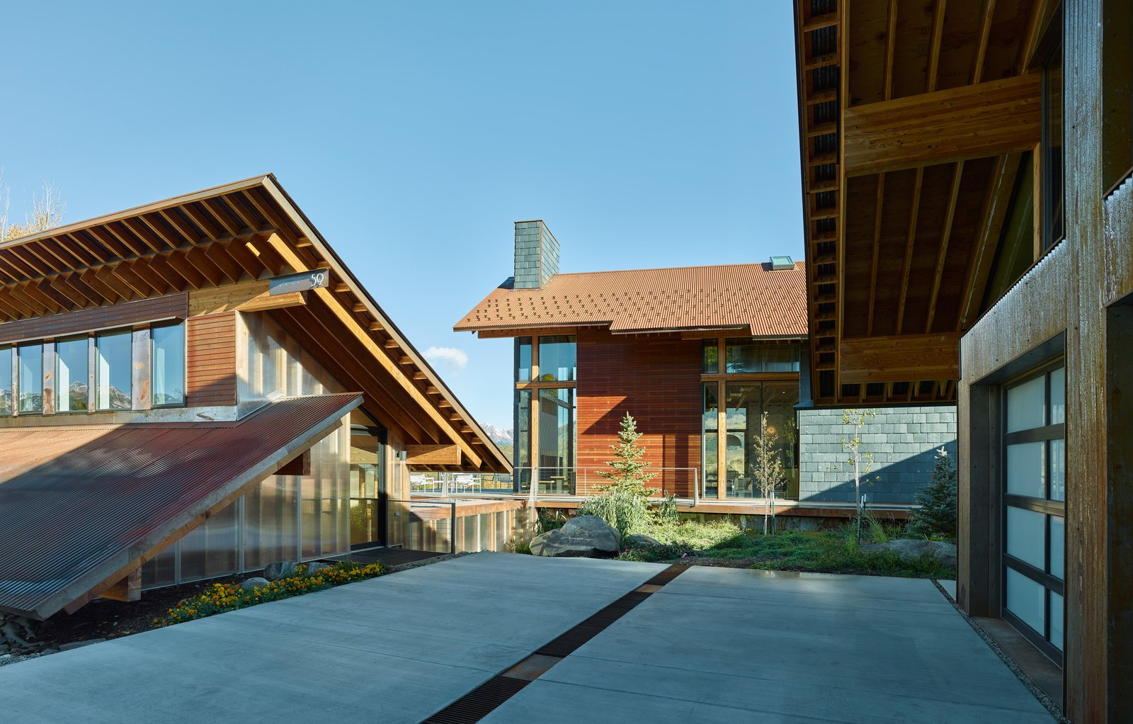 Exterior, Gable RoofLine, Shed RoofLine, and House Building Type Architect Doug Wells and his wife, Sarah, jumped at the chance to turn a former homeowners' association clubhouse in Colorado into a vacation retreat. The existing structure is flanked by two new prefab buildings: a garage and a main house.  Photo 2 of 9 in Self-Regulating Technology Makes Managing This Compound a Breeze
