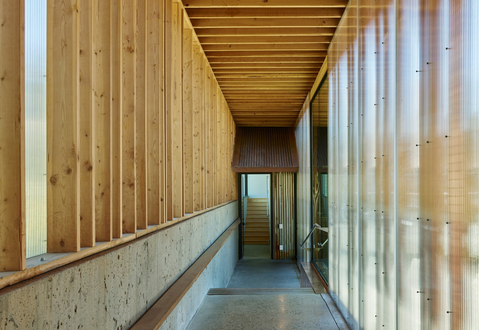 Hallway and Concrete Floor Simple passageways with polycarbonate glazing, wood framing, and polished concrete floors connect the structures.  Photo 4 of 9 in Self-Regulating Technology Makes Managing This Compound a Breeze
