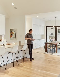 A set of Eames molded-plastic bar stools line the Caesarstone countertop in the kitchen.