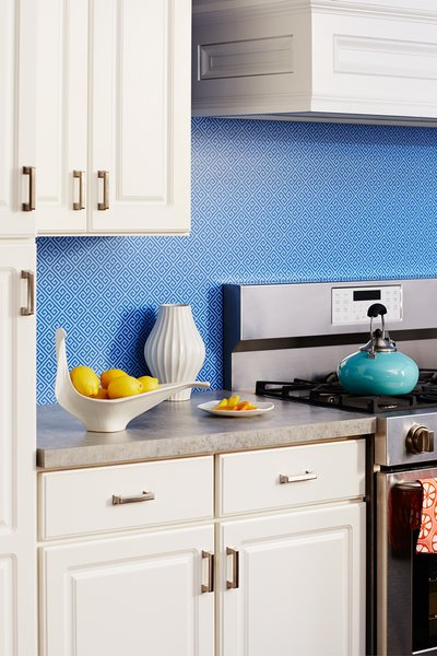 Rendered in sharp blue, the timeless motif of Greek Key is used as this kitchen's backsplash. The two-tone pattern is playful and modern against the more traditional white cabinets with molding and raised panels.