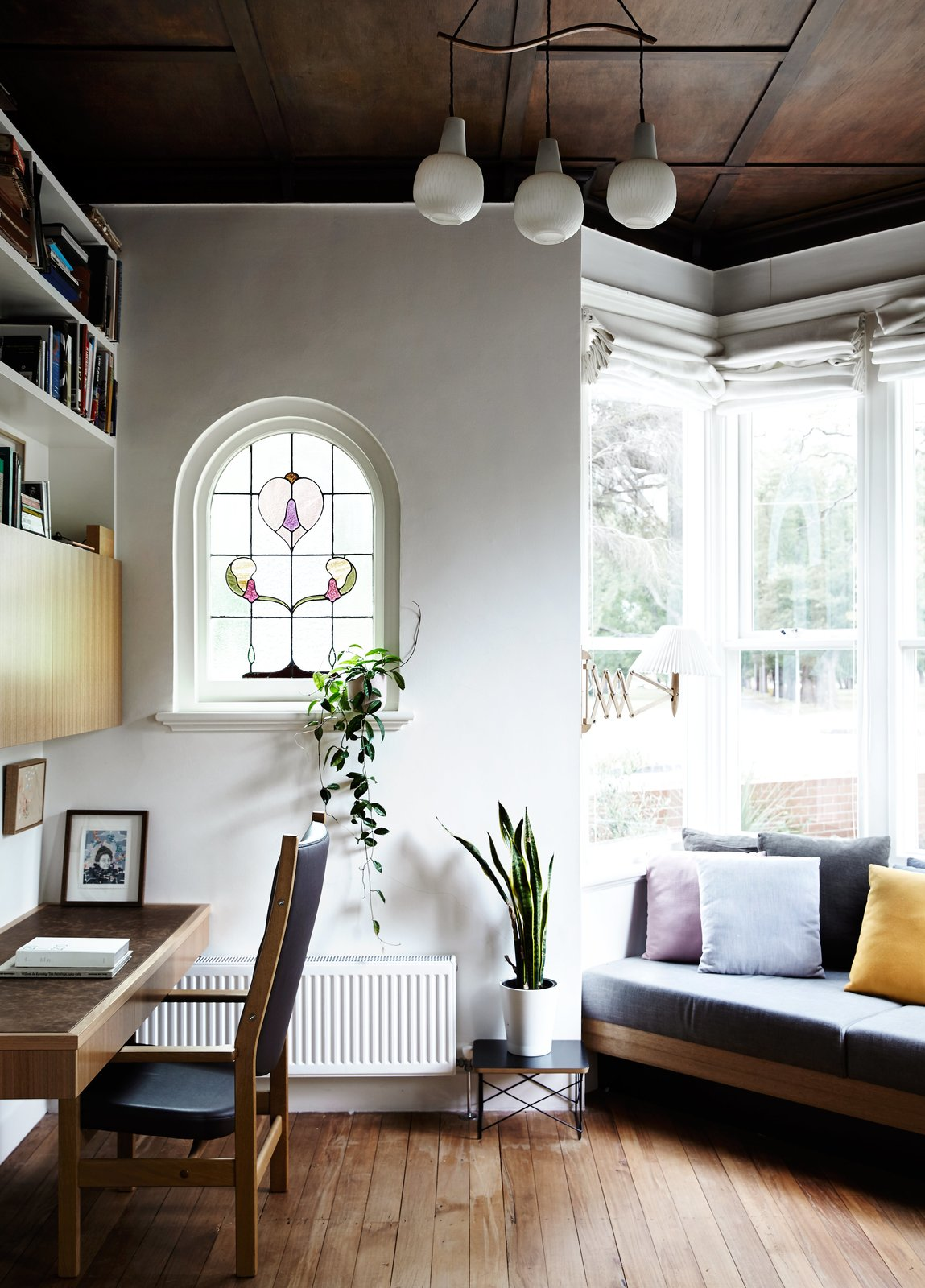 """The original coffered wood ceiling of Kate Tucker and Tom Crago's home in Melbourne, Australia, provides a dramatic backdrop for a vintage pendant from Angelucci 20th Century. """"The bay windows and high ceilings were so lovely, we really wanted to do as little as possible up front,"""" Kate says of the plan for the house.  Photo 2 of 13 in An Unassuming Edwardian Saves the Best for Out Back"""