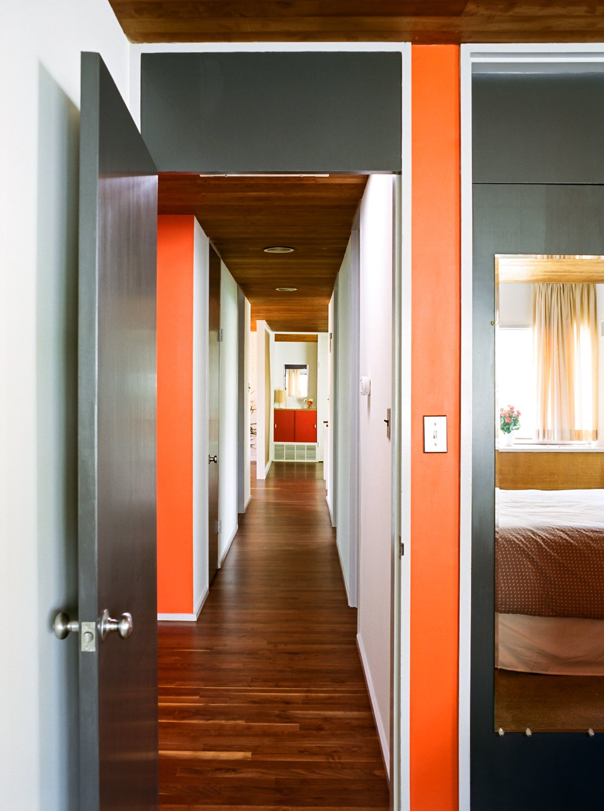 Hallway and Medium Hardwood Floor Cashmere flat paint by Sherwin-Williams was custom matched to the original chips provided by Breuer's firm—dark gray for the wood doors and MB Red for accents.  Photo 5 of 16 in Kansas City Royal