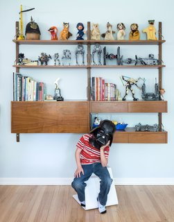 Lawrence, seven, shows off his toy collection on a vintage Cado wall unit in his bedroom,