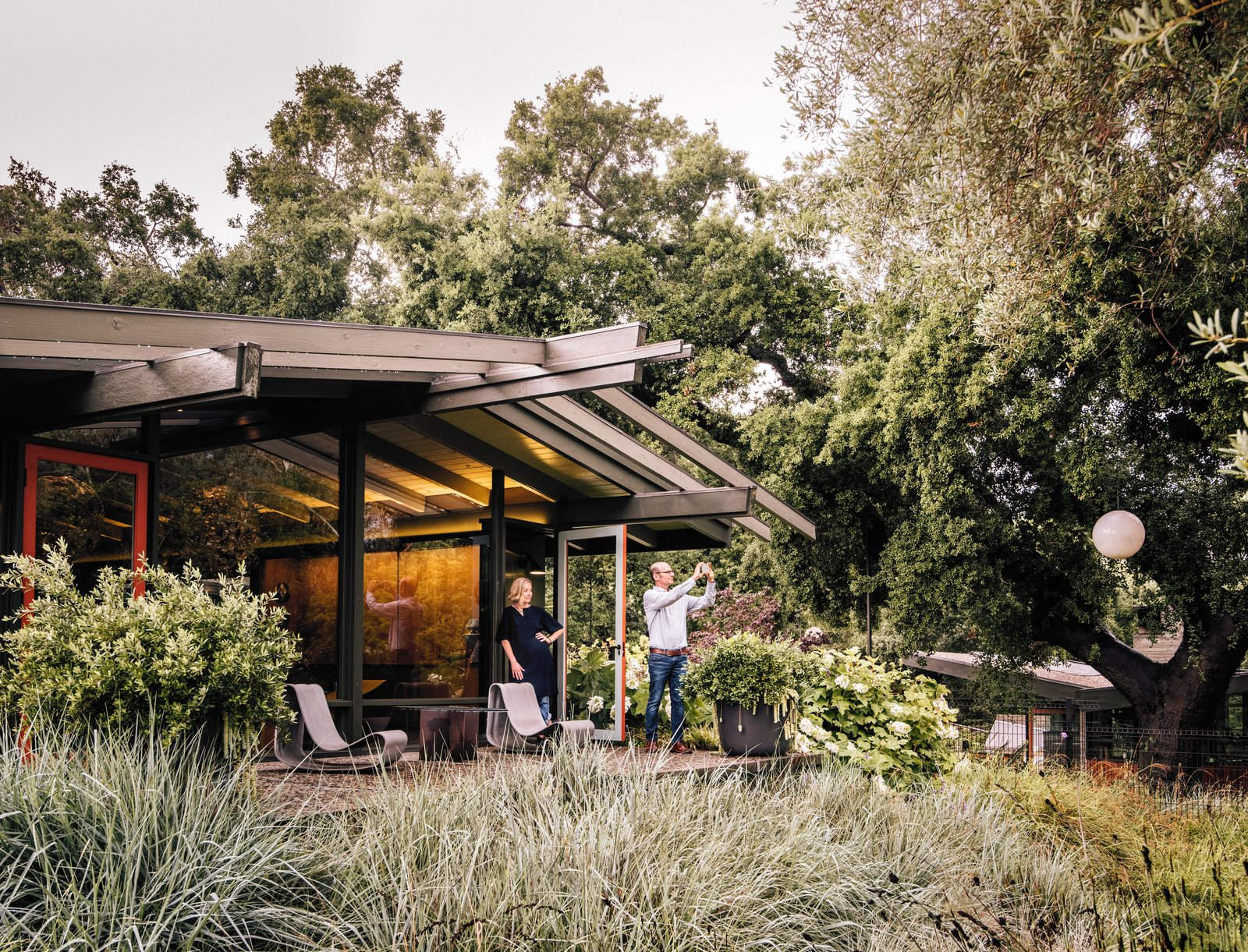 Fields of native grasses connect the main residence, situated at the top of the slope, to the new structures scattered below. Tagged: Outdoor, Back Yard, Front Yard, Side Yard, Garden, Trees, Shrubs, and Raised Planters.  Backyard Daydream from Creative Revival of a Modernist Gem
