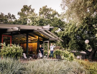 Fields of native grasses connect the main residence, situated at the top of the slope, to the new structures scattered below. A pergola extends from the post-and-beam structure that was maintained during the remodel of the midcentury home.