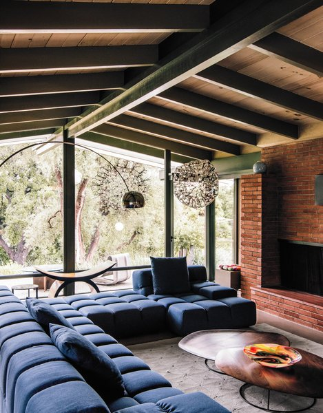 The architects maintained the midcentury post-and-beam construction and Japanese-inspired details of the original building, while brightening and expanding the interior living spaces. Patricia Urquiola's Tufty-Time sofa for B&B Italia meets Pebble coffee tables by Nathan Yong for Ligne Roset in the living room.
