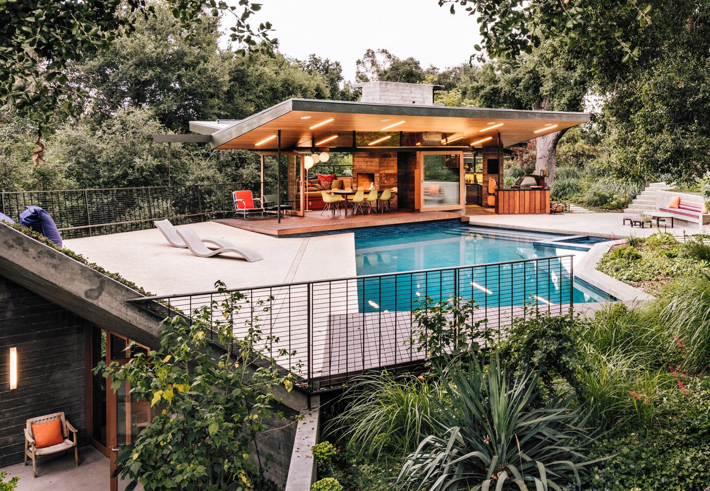 Outdoor, Back Yard, Side Yard, Front Yard, Trees, Grass, Hardscapes, Walkways, Swimming Pools, Tubs, Shower, Rooftop, Concrete Patio, Porch, Deck, Metal Fences, Wall, and Hanging Lighting Delighted with the result, they requested additional structures, including a pool house with a dining area that opens to the outdoors. Rising from the edge of the pool deck, a planted overhang shelters a gym and sauna below.  47+ Midcentury Modern Homes Across America by Luke Hopping from Creative Revival of a Modernist Gem