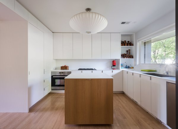 so Chris integrated a modern white design with a custom island. The oven is by IKEA; other major appliances were purchased from the Habitat for Humanity ReStore.
