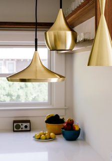 Brass pendants by Tom Dixon hang in the kitchen.