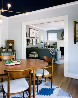 A mix of vintage and modern pieces furnish the home, including a table by Arne Vodder for George Tanier, an IKEA rug, and a Lambert & Fils chandelier in the dining room. A bar cart from her grandmother is one of Sarah's most prized possessions. The ceiling color is Benjamin Moore Marine Blue.
