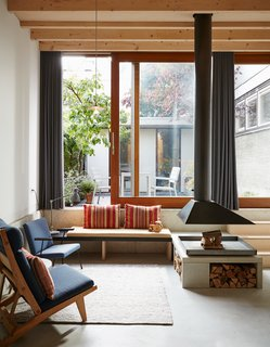 "A band of precast concrete, which holds a custom bench, wraps around the downstairs living area. The striped cushion fabric was purchased in Antwerp. A wood-framed AP71 lounge chair by Hans Wegner and a seat by Wim Rietveld, the son of famed Dutch designer Gerrit Rietveld, outfit the space. Underfloor heating installed throughout the house allows for a flexible layout: ""There aren't any radiators cluttering up the rooms,"" Jeffries explains."