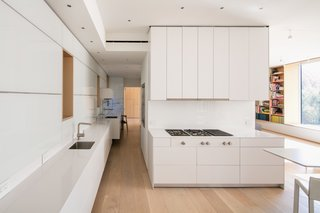 A cooktop and refrigerator from Gaggenau, Bulthaup cabinets, a Miele oven, and an Asko dishwasher outfit the all-white kitchen, which is located on the entry-level floor.