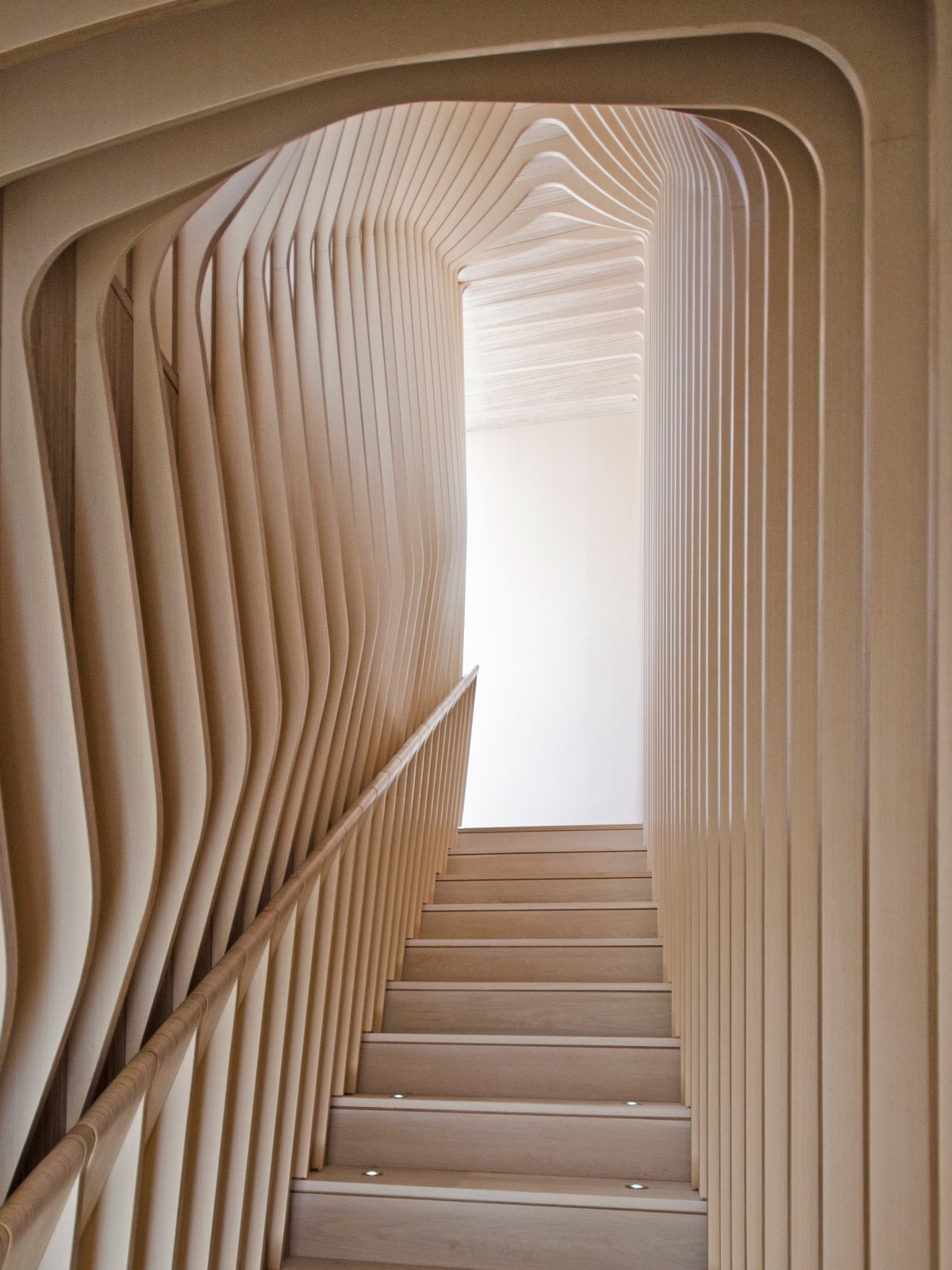 Staircase, Wood Tread, and Wood Railing Though they give the appearance of bent plywood, each curved layer of the ribbed corridor was constructed with flat, laminated cutouts, including the rounded hand rail.  Best Photos from What's the Twist Behind This Home's Sinuous Staircase? Ordinary Plywood
