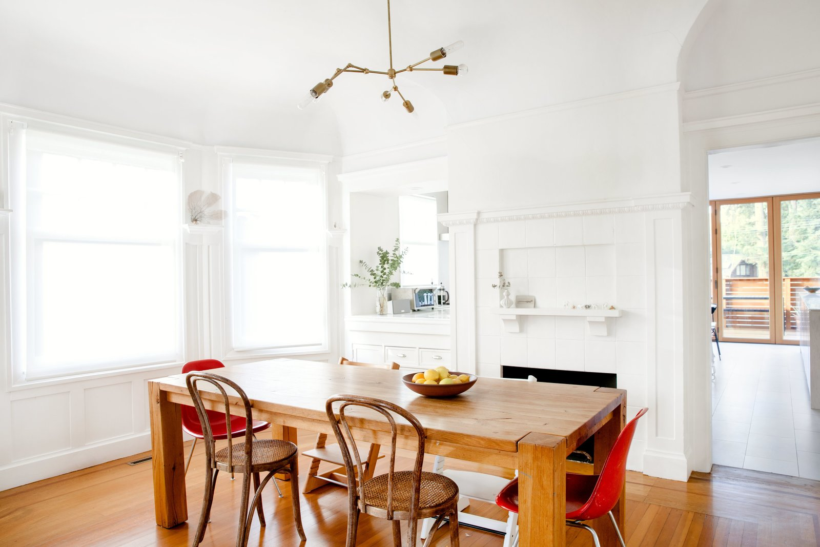 Dining Room, Pendant Lighting, Table, Chair, Medium Hardwood Floor, and Standard Layout Fireplace Three furniture icons, in pairs, surround the dining room table: the Eames Side, Thonet No. 14, and Peter Opsvik Tripp Trapp chairs.  Photo 3 of 14 in Check Back
