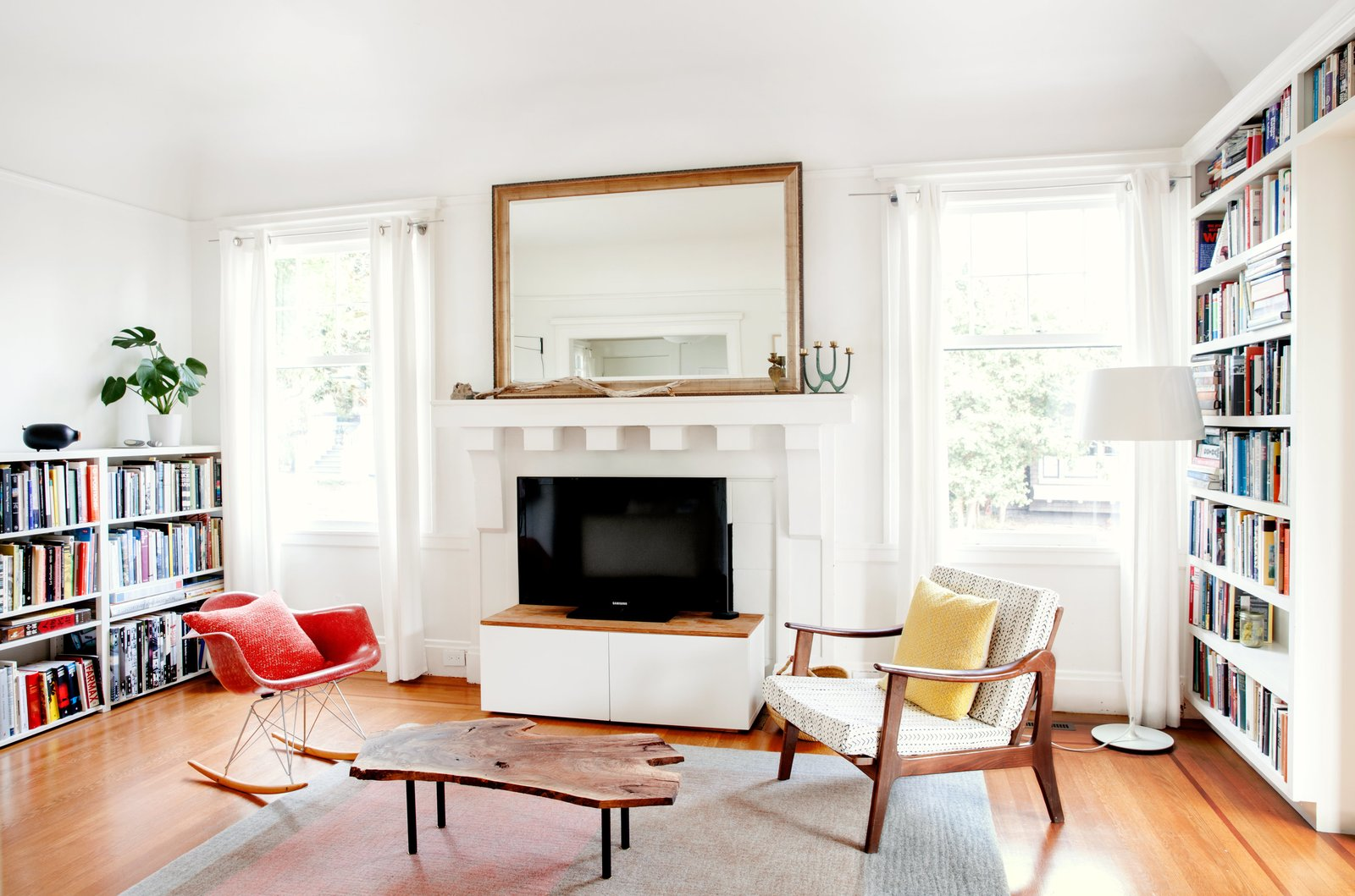 Living Room, Chair, Coffee Tables, Standard Layout Fireplace, Medium Hardwood Floor, Floor Lighting, Rug Floor, Bookcase, and Lamps focusing attention on an Eames rocker, a rug by Peace Industry, and a live-edge coffee table by Cheng+Snyder. TKTKTKTK  Photo 8 of 15 in Check Back