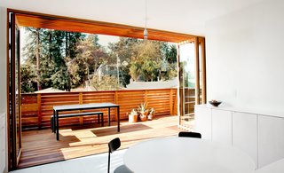 A proposed wall of sliding glass doors morphed into a NanaWall system after the residents were assured the latter was more likely to be approved by the town. When folded back, the panels provide a seamless connection to the deck.