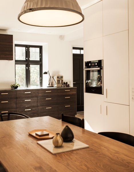 Kitchen, Pendant Lighting, Wood Counter, White Cabinet, and Wood Cabinet Lisette Bernhoft of Design by Us planned the kitchen. The smoked oak cabinets are topped with lava stone. The pulls are brass.  Modern Danish Homes We Love from Urban Renewal
