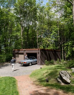 For the garage, the couple replaced rotted timbers, swapped in new gutters, and stained the exterior Cordovan Brown by Benjamin Moore to match the home and pool house.