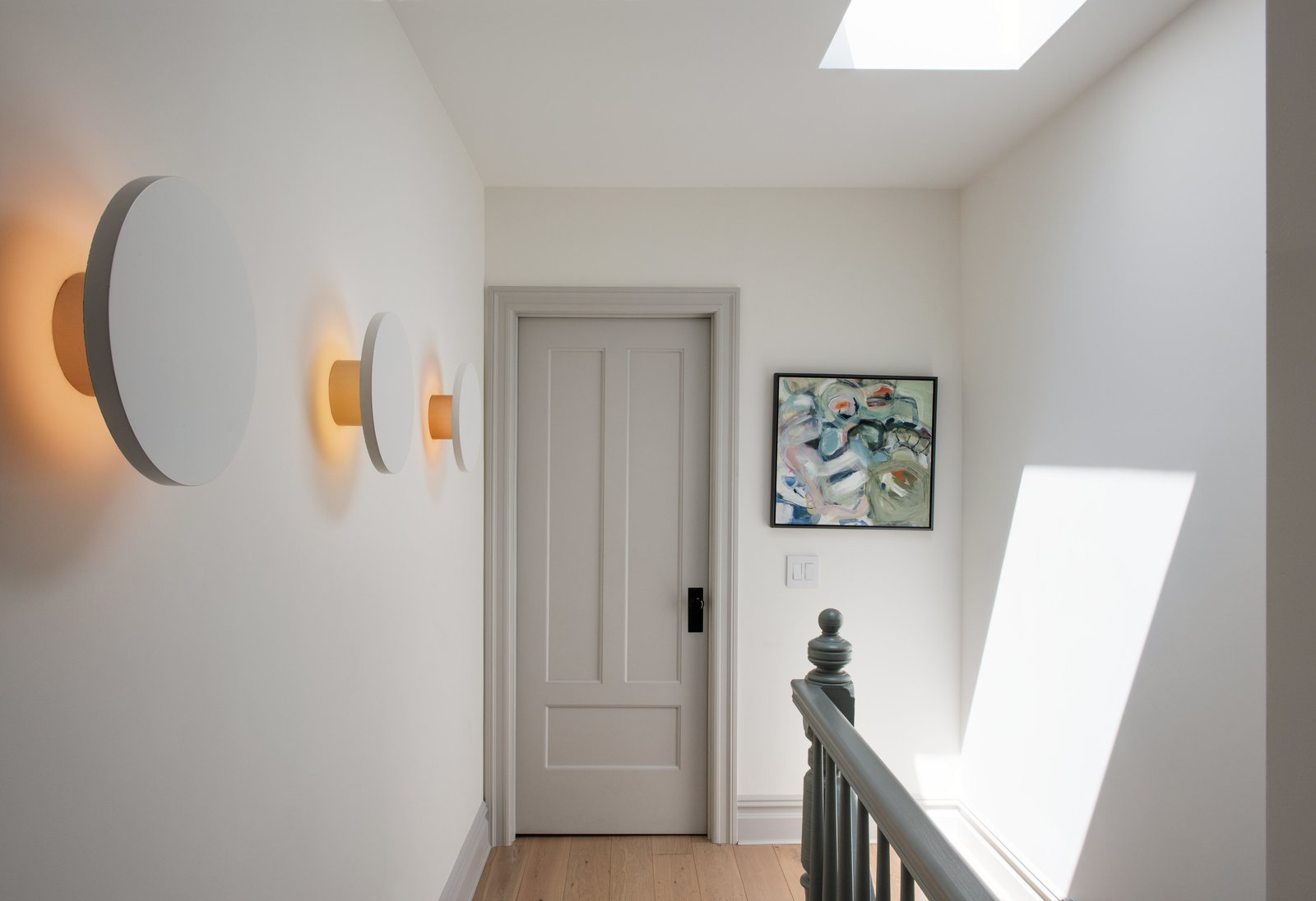 Hallway and Light Hardwood Floor A series of Radient sconces by RBW illuminates the third-floor landing with a subtle graphic pop.  Photo 8 of 14 in Modern Becomes Eclectic in This Renovated Brooklyn Townhouse