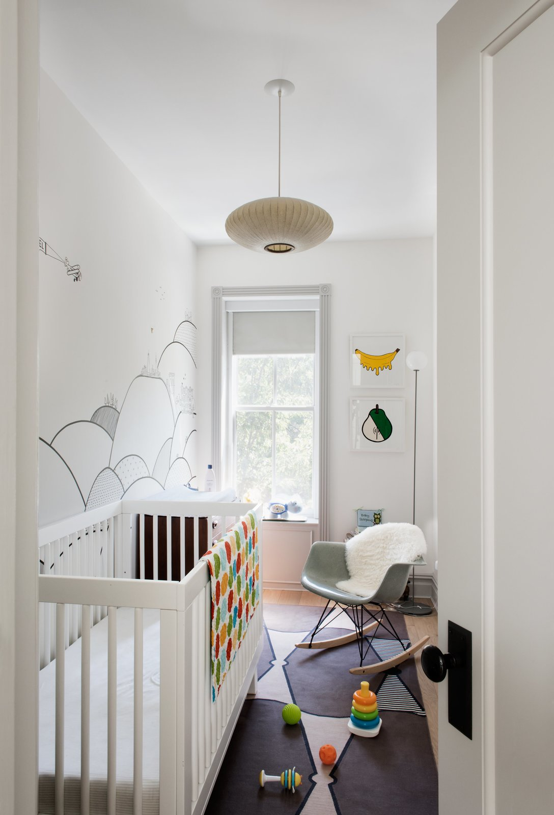 Kids Room, Bedroom Room Type, Bed, Rockers, Medium Hardwood Floor, Toddler Age, and Neutral Gender A mural by local illustrator Kale Williams—a good friend and the wife of one of Brill's partners—provides the backdrop forthe nursery.  Photo 10 of 14 in Modern Becomes Eclectic in This Renovated Brooklyn Townhouse