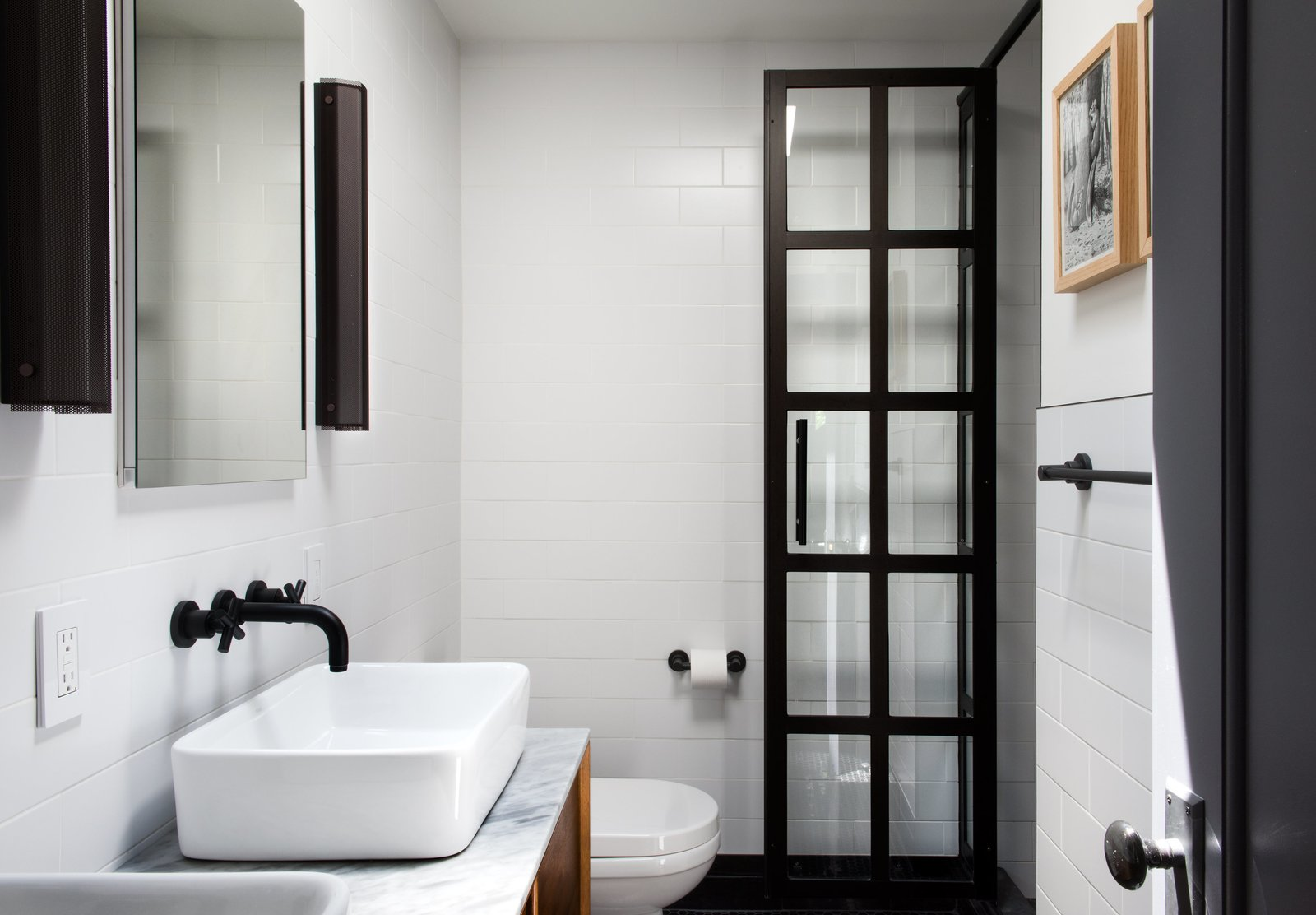 Bath Room, Marble Counter, Vessel Sink, and Subway Tile Wall An austere palette defines the master bathroom, with subway tiles from Classic Tile New York, matte-black fixtures by California Faucets, and black perforated-aluminum Branch sconces by RBW.  Bathroom from Modern Becomes Eclectic in This Renovated Brooklyn Townhouse