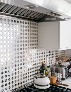 In an otherwise mostly white kitchen, the mirrored concrete tile backsplash introduces an unexpected element. The floor is also covered with the same tile from Mission Tile West, giving a fun, almost disco-like vibe to the space.