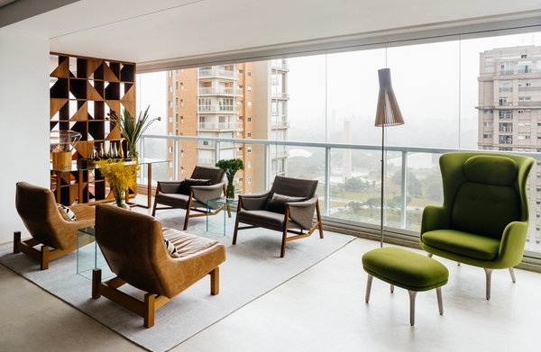 In an apartment overlooking São Paulo's Ibirapuera Park—completed in 1954 to commemorate the city's 400th anniversary—the furniture is as distinctive as the view. Architect Flavio Castro of FCstudio worked closely with the residents to update and outfit the home, which is appointed with a mix of contemporary and Brazilian modern classics. A pair of Sérgio Rodrigues's Paraty armchairs (in foreground)—designed for Brasilia's Itamaraty Palace in 1963—face a duo of Jader Almeida's Isa armchairs in the living area. The green Ro lounge and ottoman are by Jaime Hayon for Fritz Hansen.