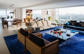 Furniture groupings and bright, dramatic accents—like the sapphire banana-fiber rug by Kamy Maison in the main living area—further divide the interior into distinct yet flexible stations. The trio of seating options includes wood-and-cane Cosme Velho armchairs by Claudia Moreira Salles, a plush Soft Dream leather sofa by Antonio Citterio for Flexform, and a blue Fergana sofa by Patricia Urquiola for Moroso. Just beyond, a Fina table, also by Salles, joins Marta chairs by Aristeu Pires and Torch pendants by Sylvain Willenz to form the dining area.