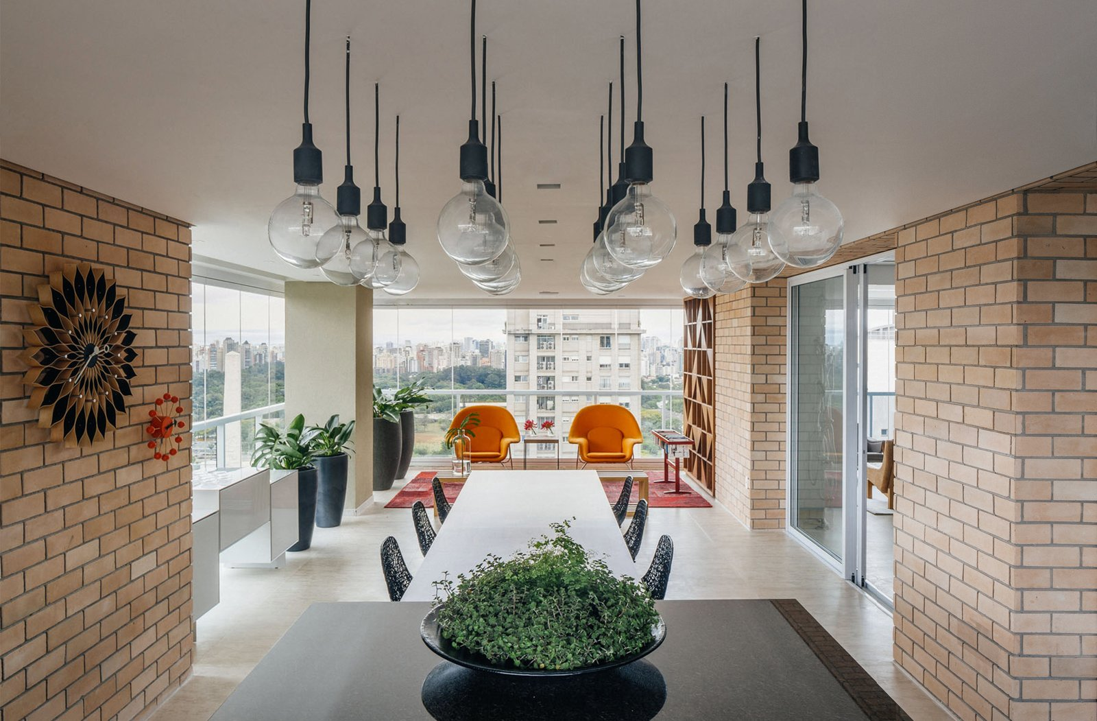 Outdoor, Large Patio, Porch, Deck, and Hanging Lighting On the terrace, a custom mixed-height table made from wood and granite encourages a communal cooking and dining experience.  Photo 8 of 9 in Overlooking a Niemeyer Masterpiece, This Flat is Filled with Brazilian Modern Gems